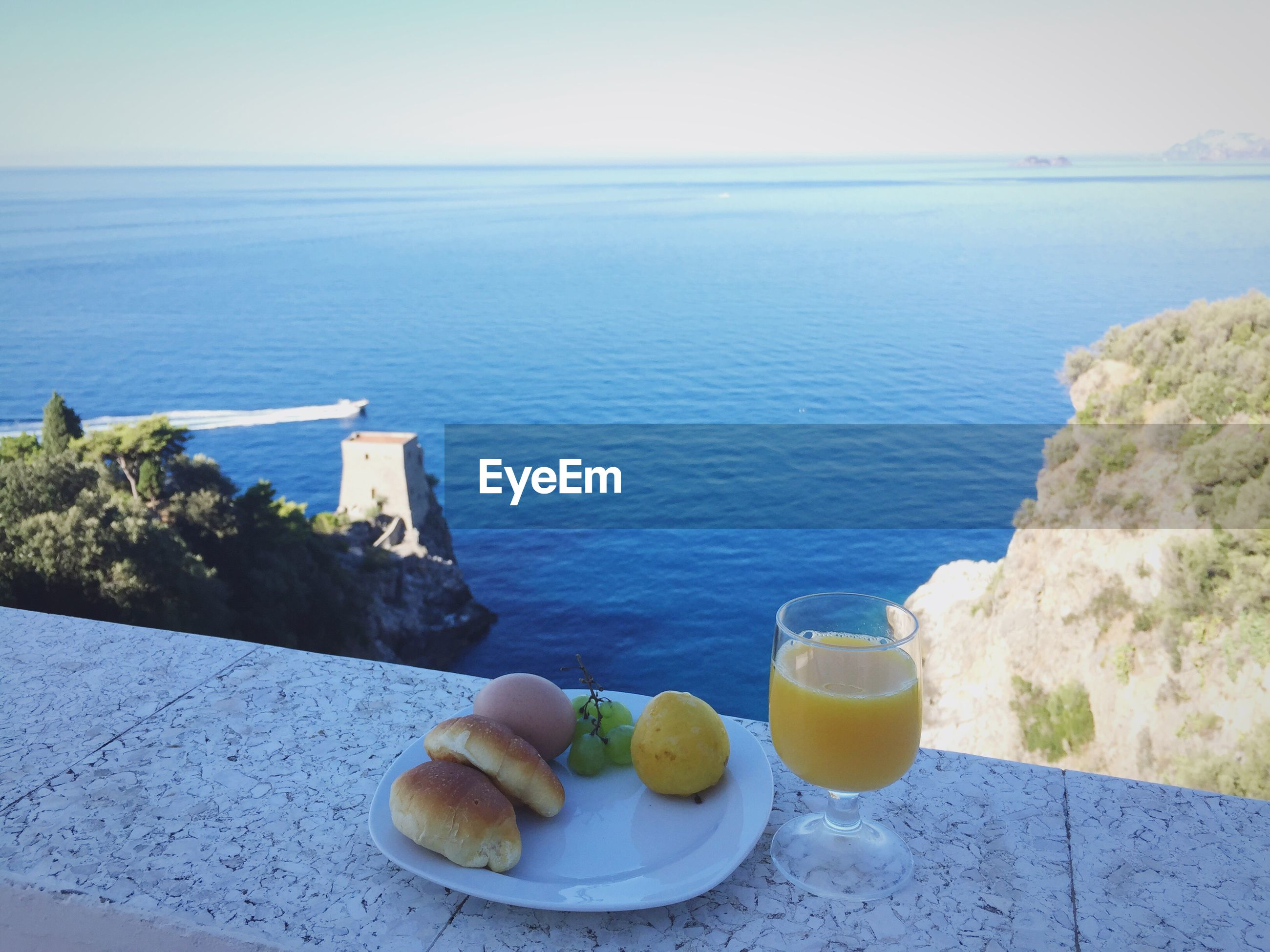 Breakfast on retaining wall by sea against sky