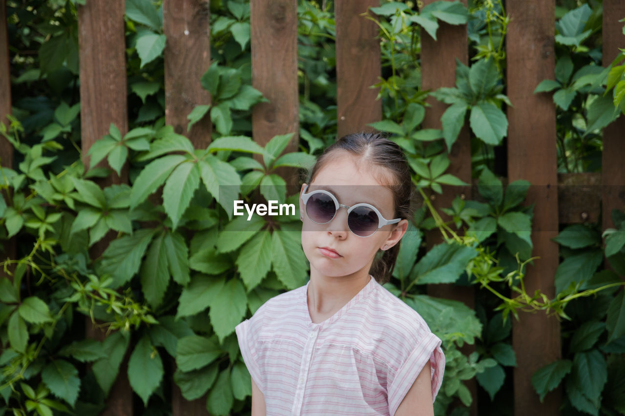sunglasses, one person, portrait, glasses, plant, plant part, leaf, fashion, real people, front view, lifestyles, headshot, day, looking at camera, leisure activity, young adult, nature, young women, women, outdoors, teenager, hairstyle, beautiful woman