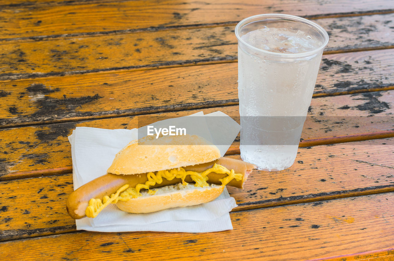 Close-up of hot dog and drink on table