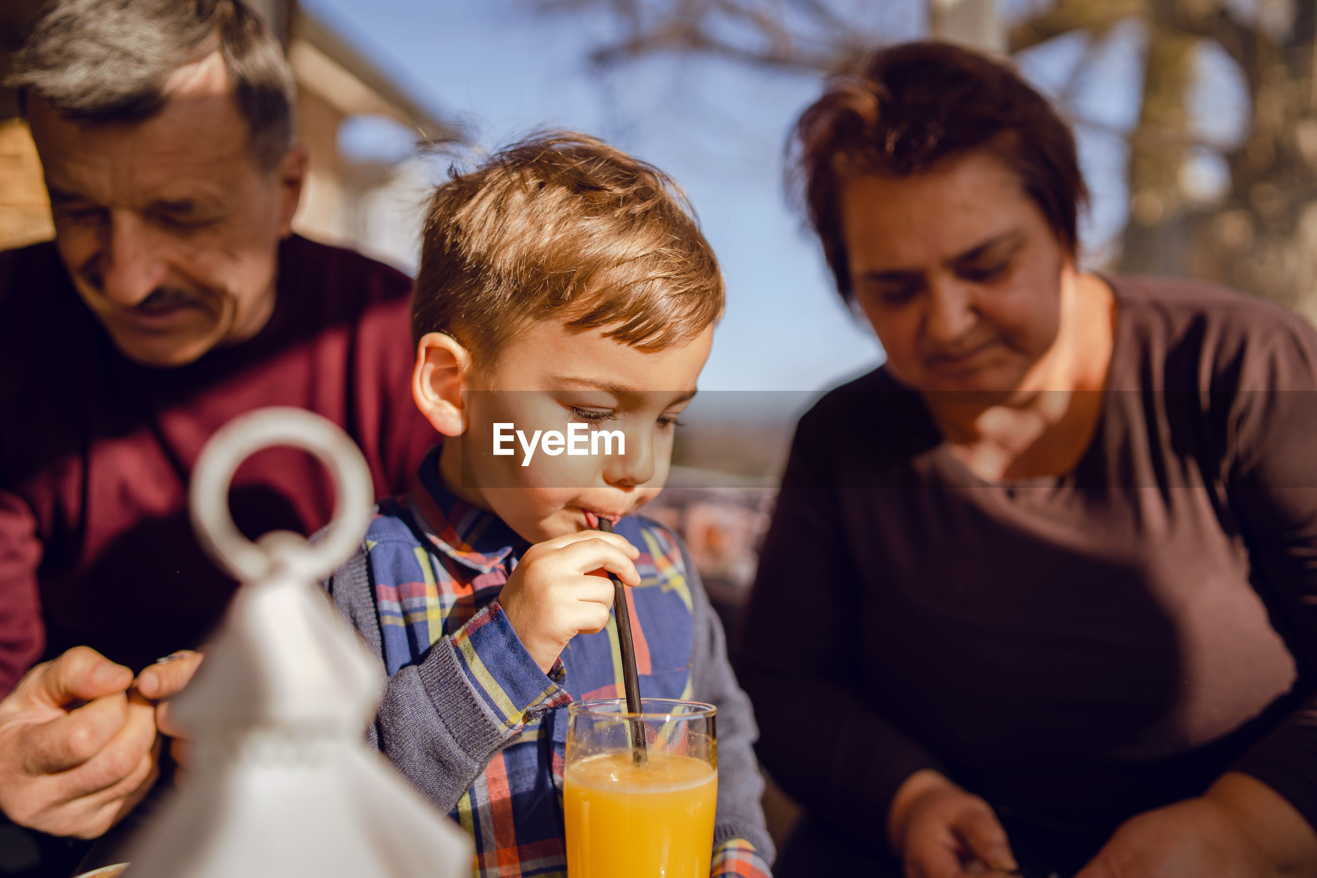Boy drinking juice while having breakfast with grandparents at home