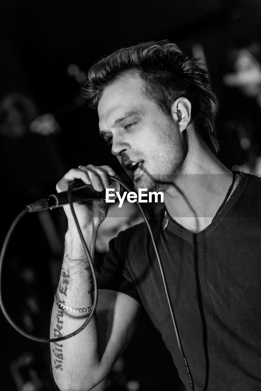 one person, real people, focus on foreground, men, music, beard, young men, tattoo, young adult, lifestyles, leisure activity, waist up, indoors, arts culture and entertainment, facial hair, casual clothing, adult, performance, nightlife, rock music, festival