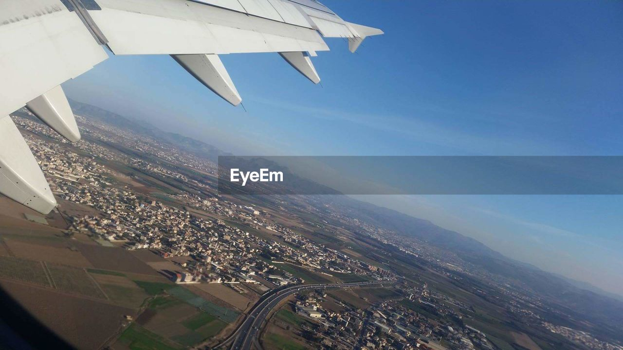 airplane, flying, air vehicle, transportation, mode of transportation, landscape, environment, aircraft wing, nature, sky, architecture, travel, aerial view, city, day, motion, on the move, journey, building exterior, mid-air, no people, outdoors, cityscape, plane