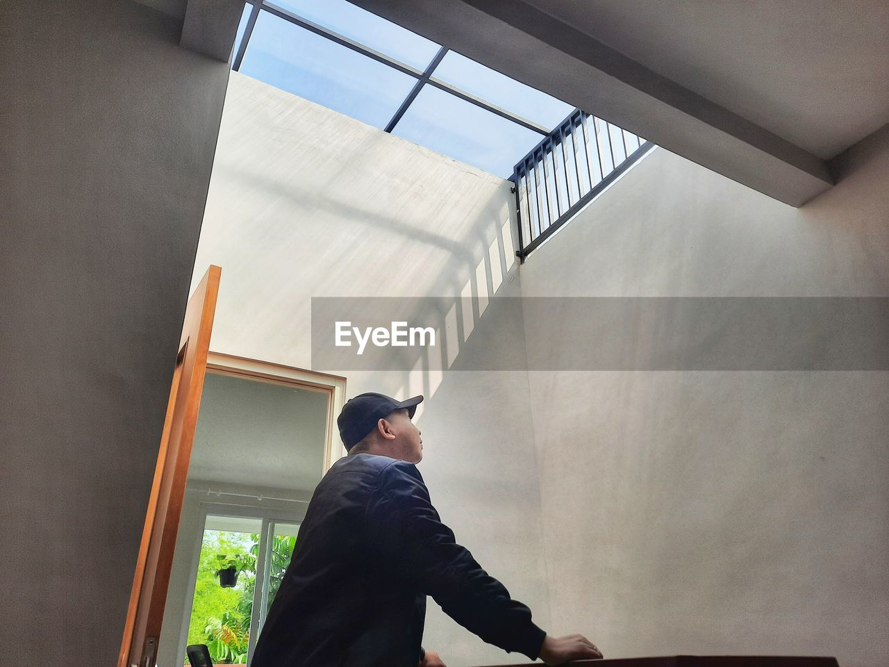 LOW ANGLE VIEW OF MAN LOOKING THROUGH WINDOW AT WALL