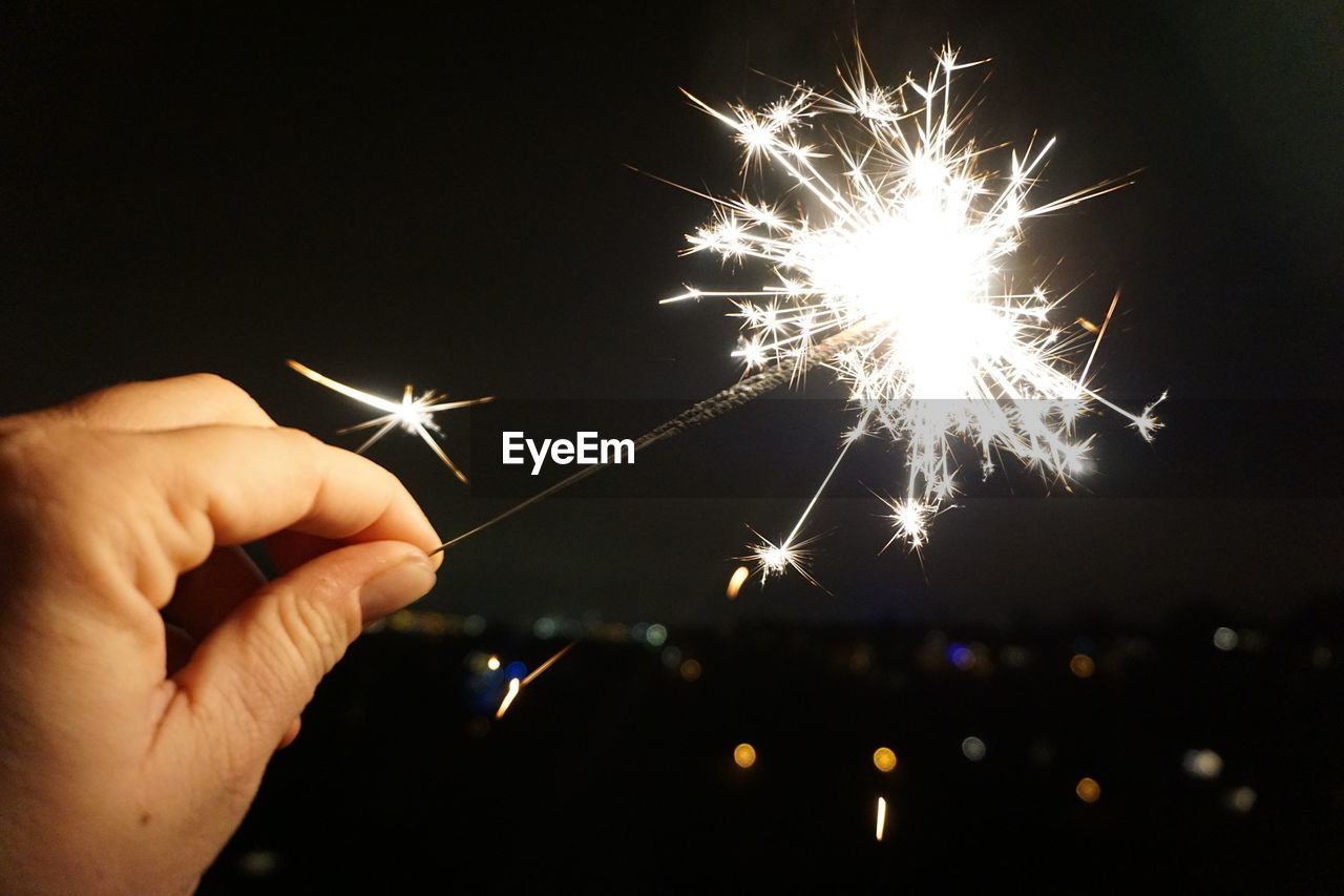 human hand, celebration, illuminated, night, firework - man made object, sparks, holding, human body part, sparkler, firework display, glowing, long exposure, human finger, real people, exploding, firework, burning, one person, celebration event, motion, event, diwali, outdoors, christmas, lifestyles, sky, close-up, people