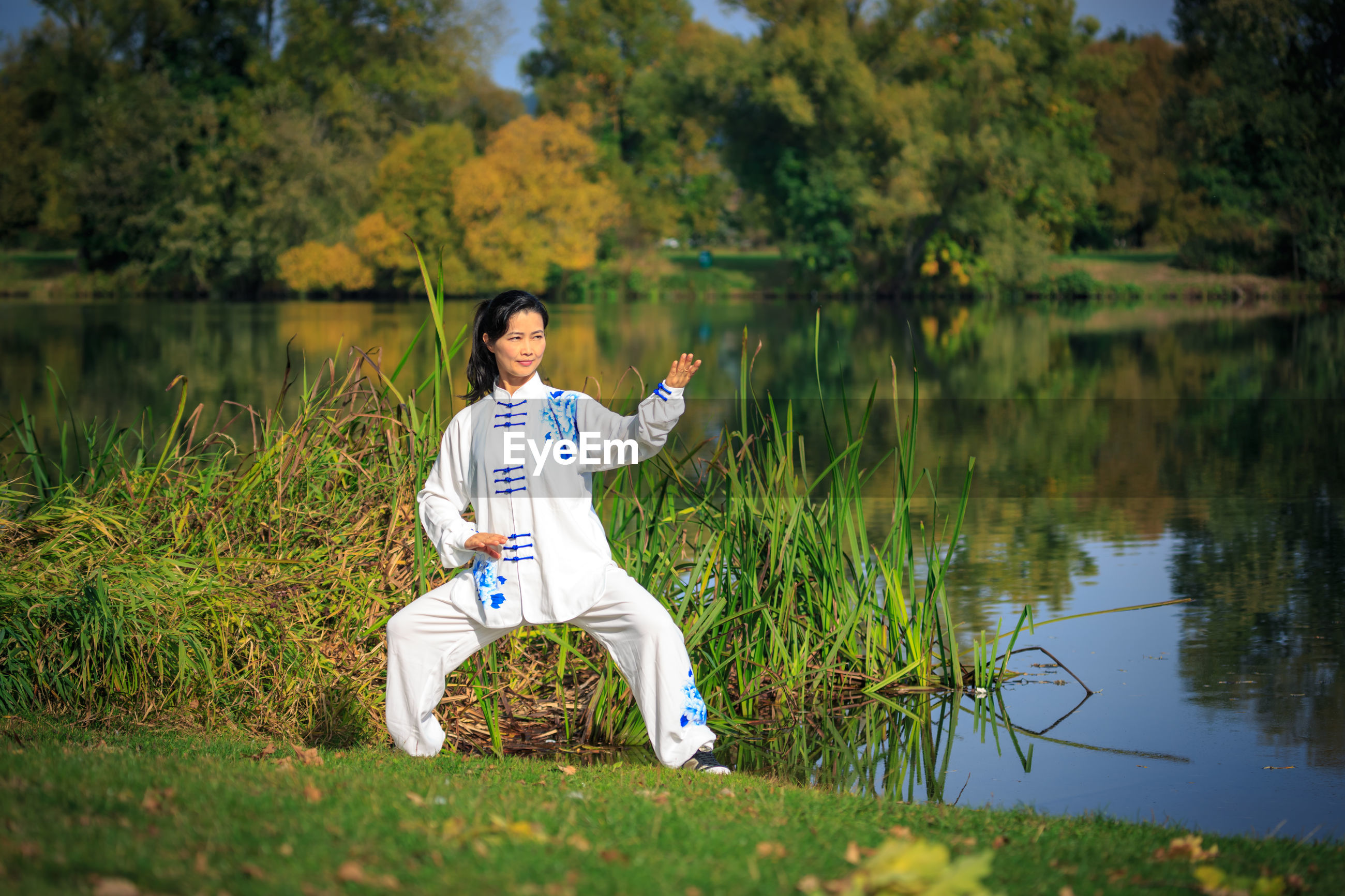 Full length of woman practicing martial arts while standing at lakeshore