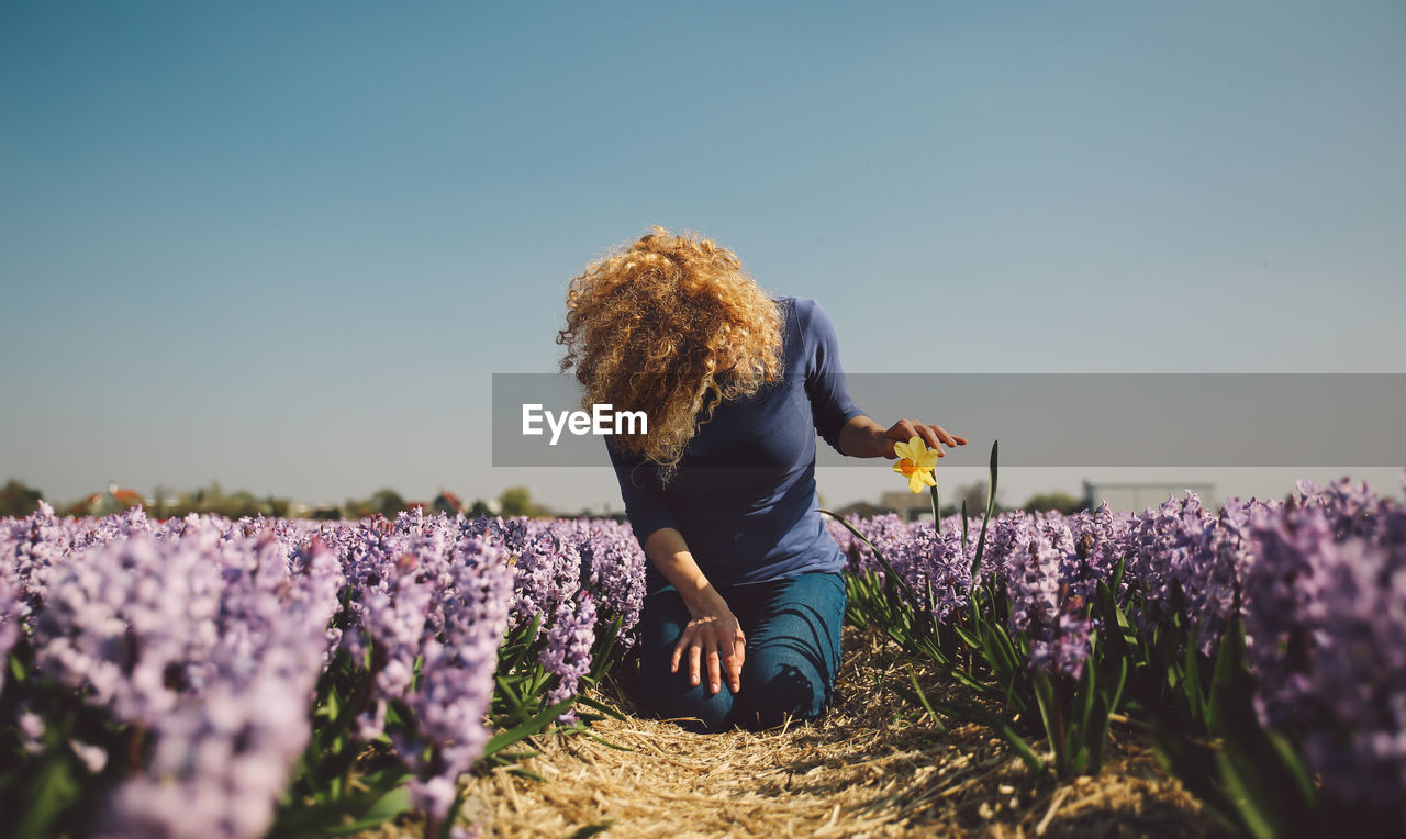 Woman With Flowers On Field Against Clear Sky