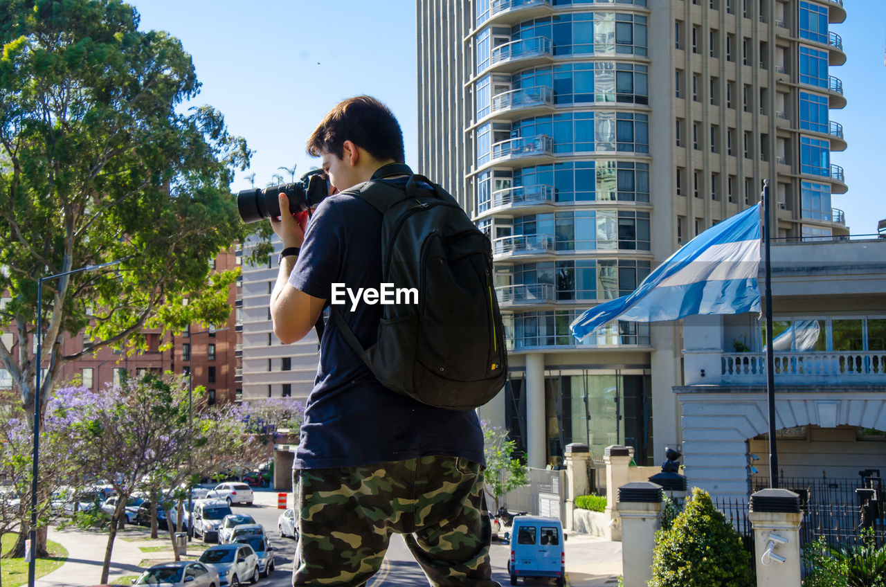 real people, building exterior, architecture, built structure, rear view, one person, tree, standing, leisure activity, outdoors, men, day, lifestyles, city, casual clothing, photographing, camera - photographic equipment, technology, photography themes, nature, young adult, sky