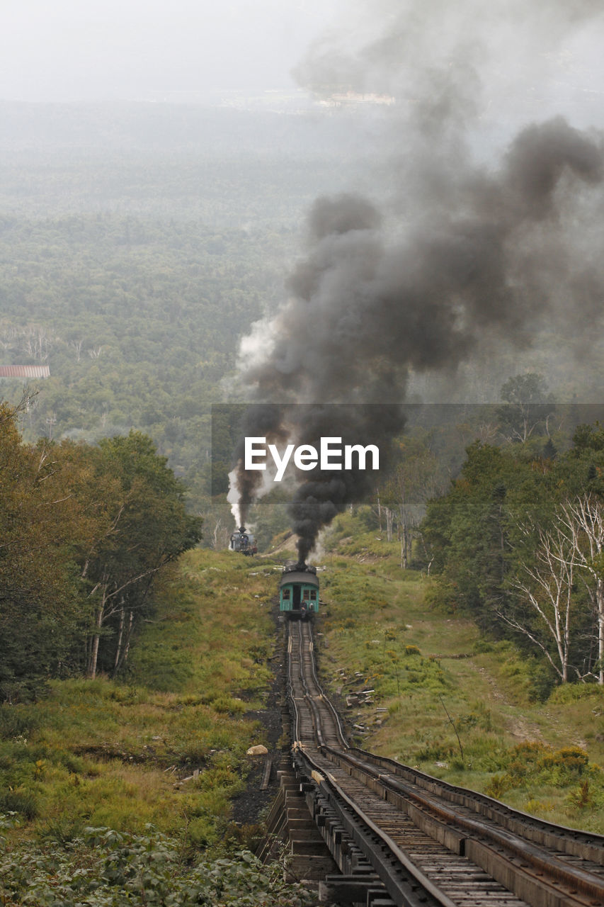 smoke - physical structure, rail transportation, track, pollution, tree, railroad track, nature, environment, day, emitting, plant, environmental issues, land, no people, sky, air pollution, architecture, built structure, high angle view, building exterior, outdoors