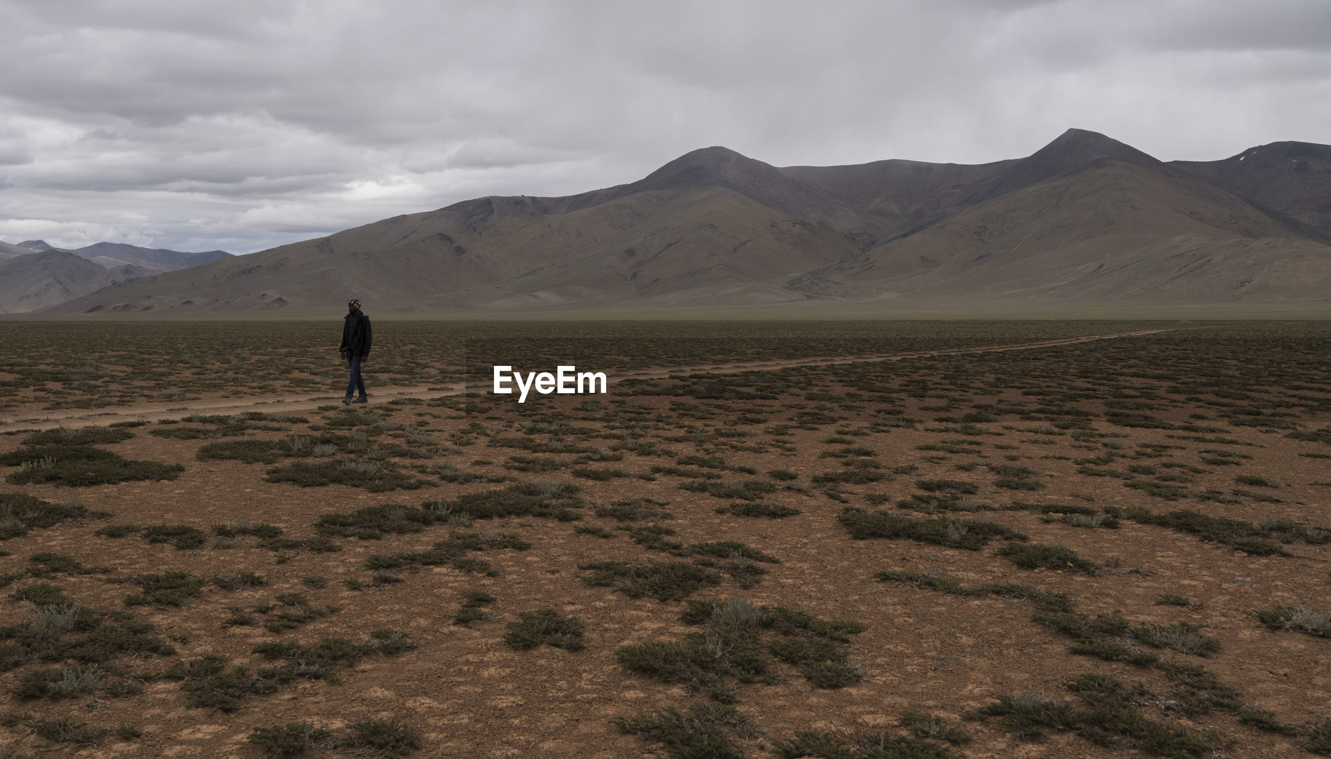 Man walking at desert against mountains