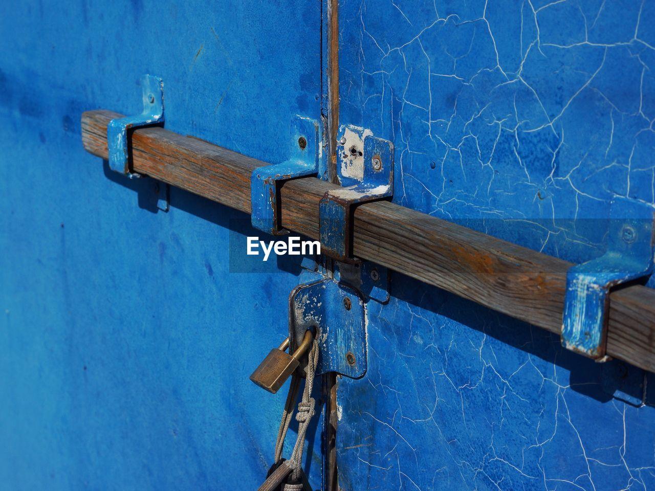 Close-Up Of Padlocks On Blue Metallic Structure