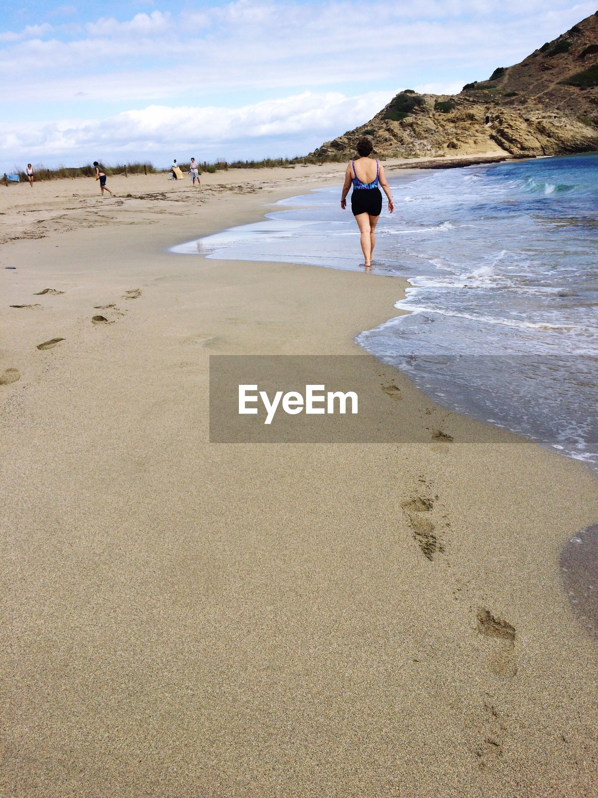 Full length rear view of woman walking at beach against sky