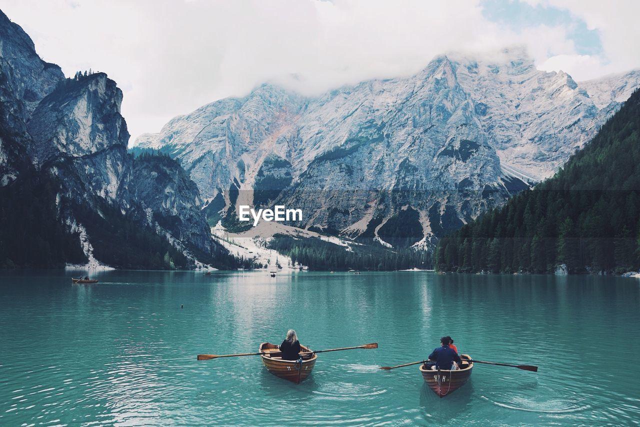 Rear View Of Man And Woman Sailing Boats In Lake