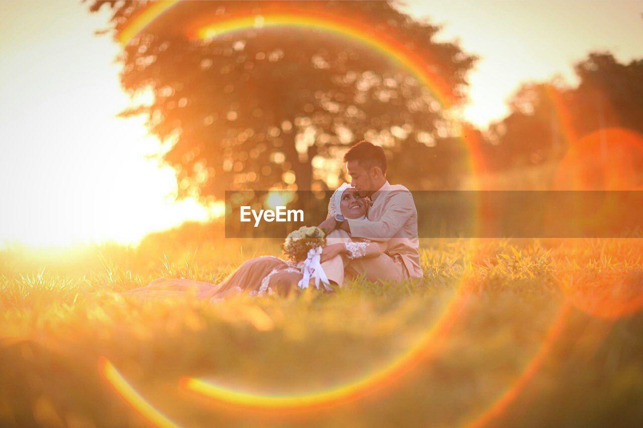 Wedding couple sitting on grassy field