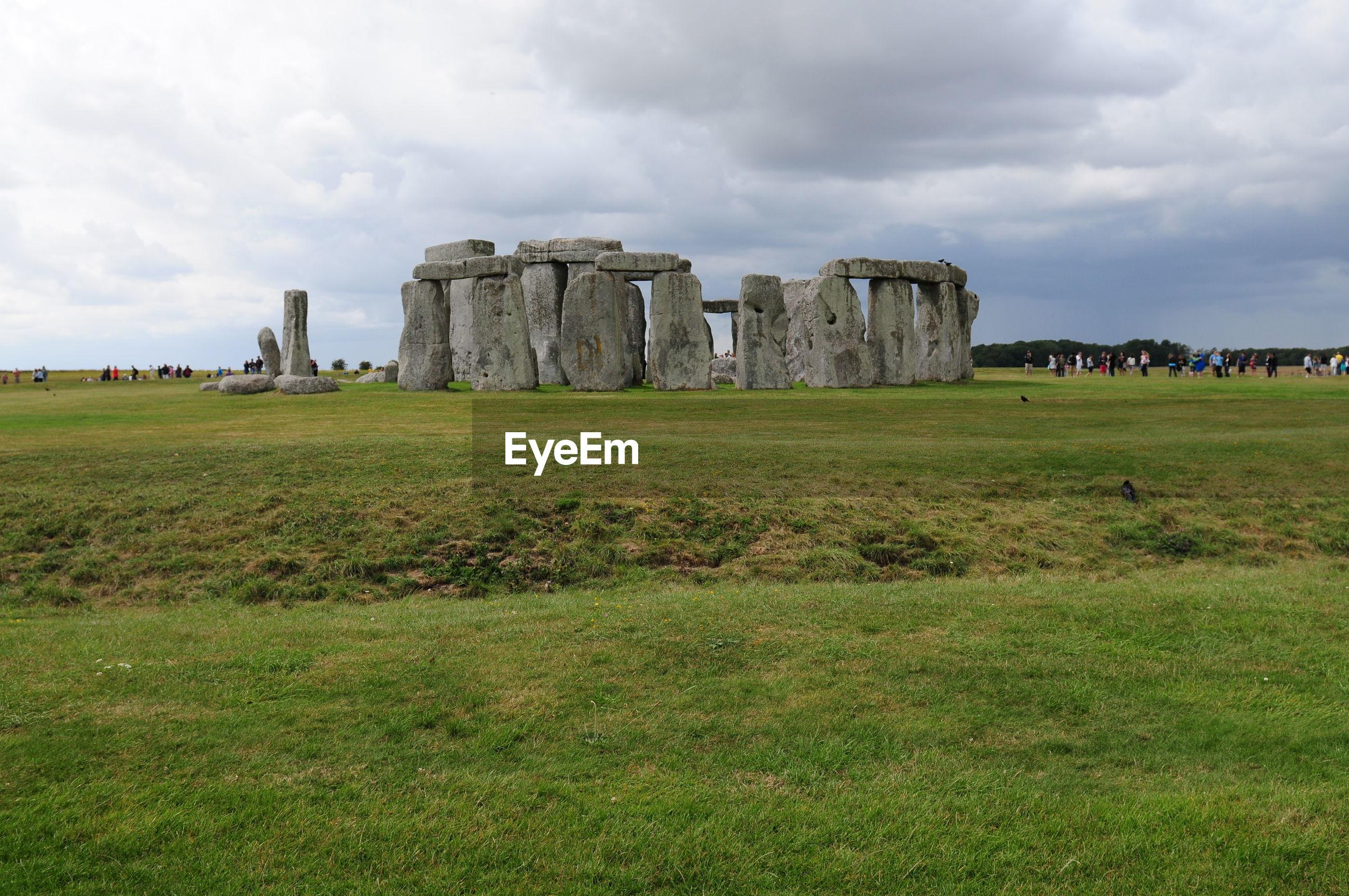 Stonehenge on grassy field against sky