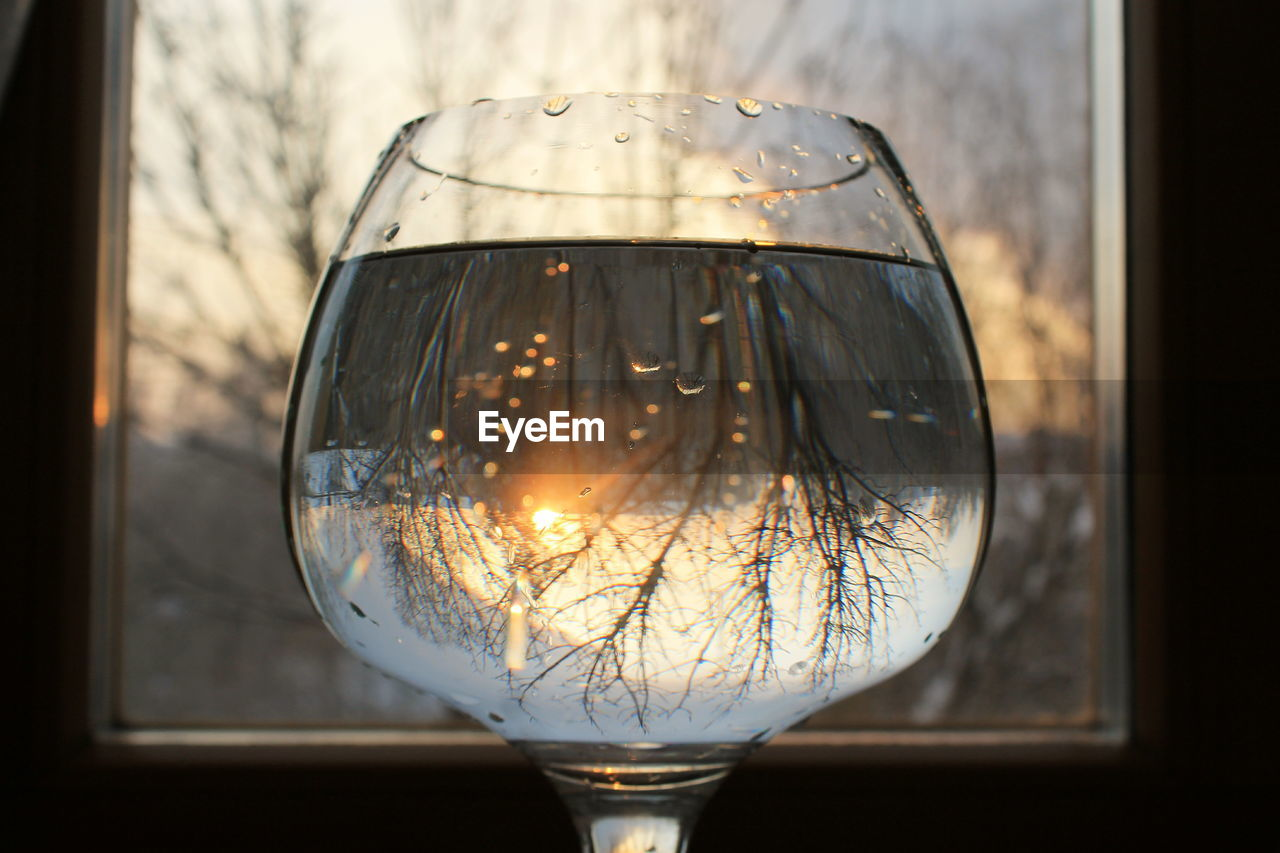 Close-Up Of Drink In Wineglass With Reflection Against Window