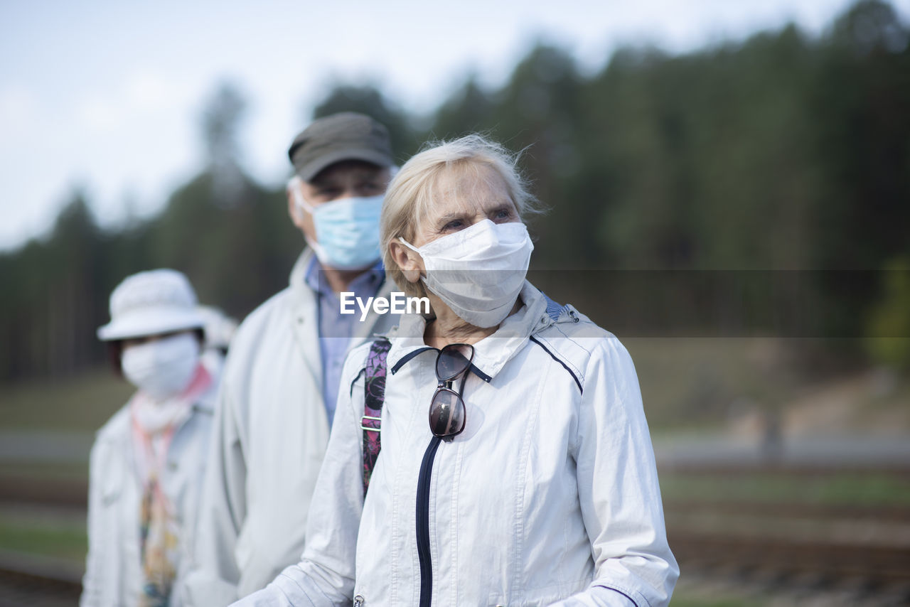 Group of elderly seniors people with face masks waiting train before traveling during a pandemic