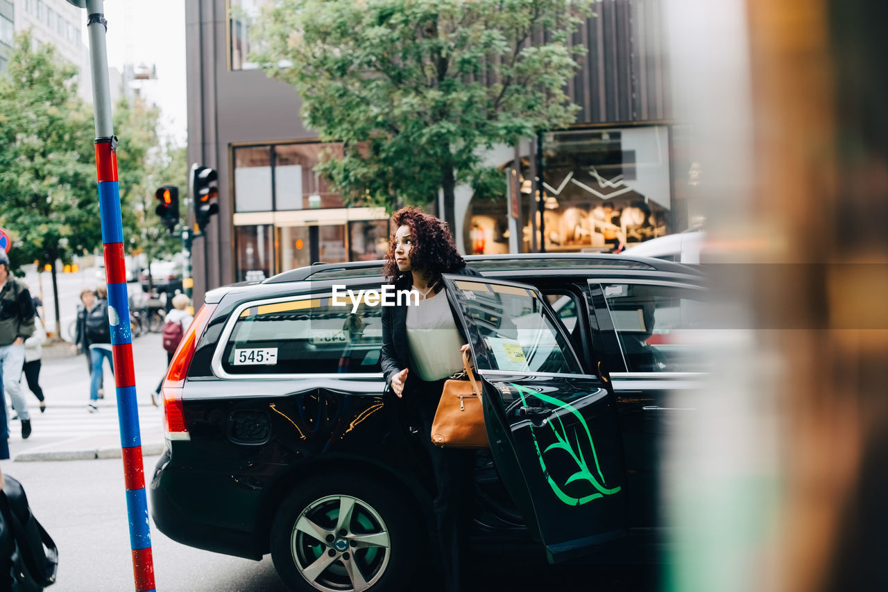 Mid adult businesswoman disembarking from taxi on street in city