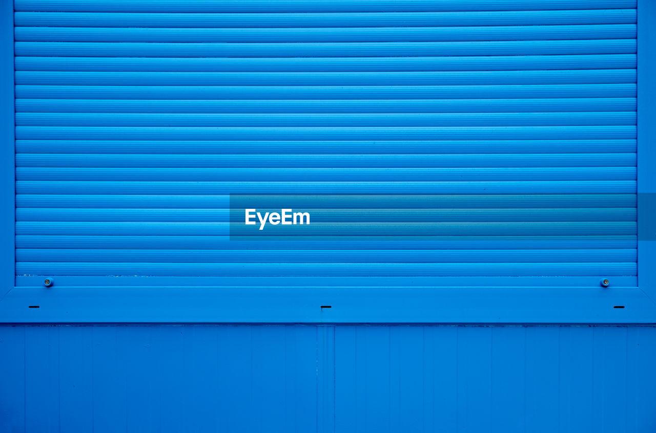 Full Frame Shot Of Shutter On Blue Wall