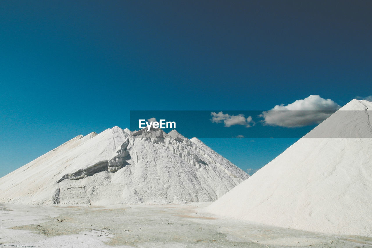 Salt collected on field against blue sky