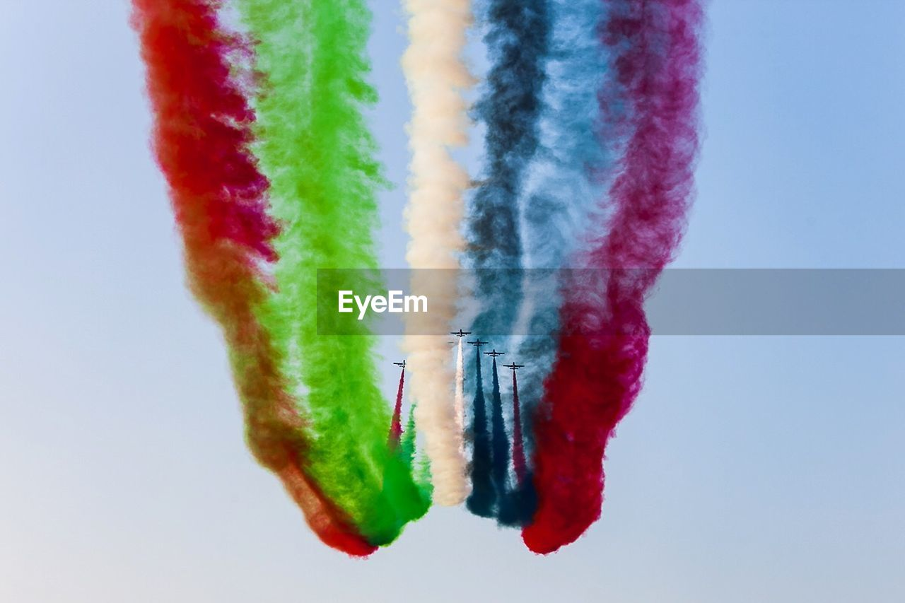multi colored, airshow, low angle view, sky, flying, mid-air, no people, clear sky, day, air vehicle, outdoors, blue, teamwork, vapor trail, military airplane, airplane, aerobatics, fighter plane