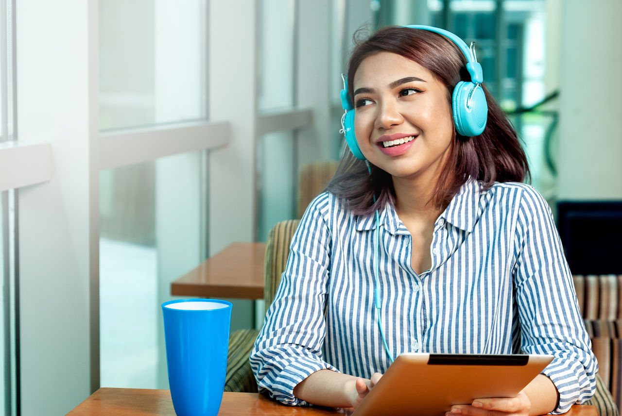 Smiling woman listening music while using digital tablet at table