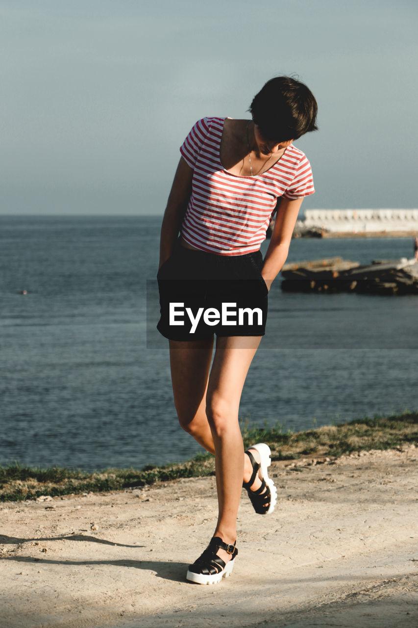 Full Length Of Woman Walking By Sea