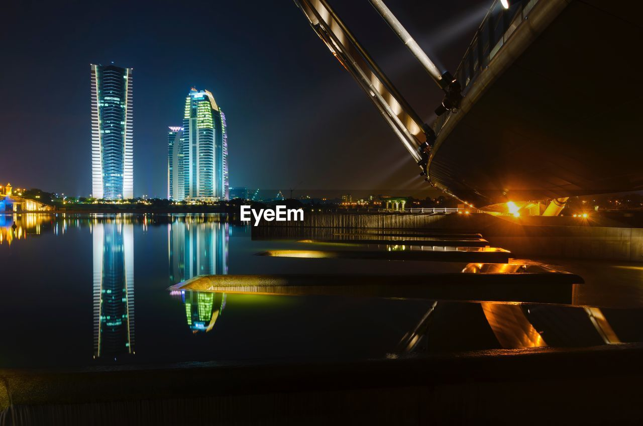 illuminated, reflection, night, architecture, built structure, water, building exterior, skyscraper, city, no people, waterfront, travel destinations, modern, river, outdoors, urban skyline, sky, cityscape, clear sky