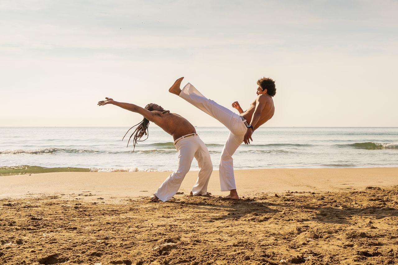 Full length of two men performing martial arts at beach against sky