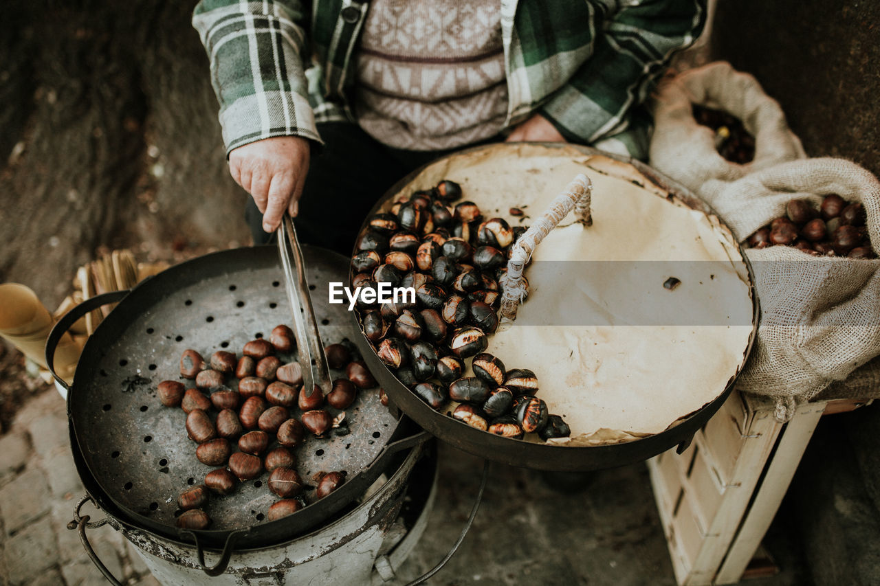Close-Up Of Person Roasting Chestnuts