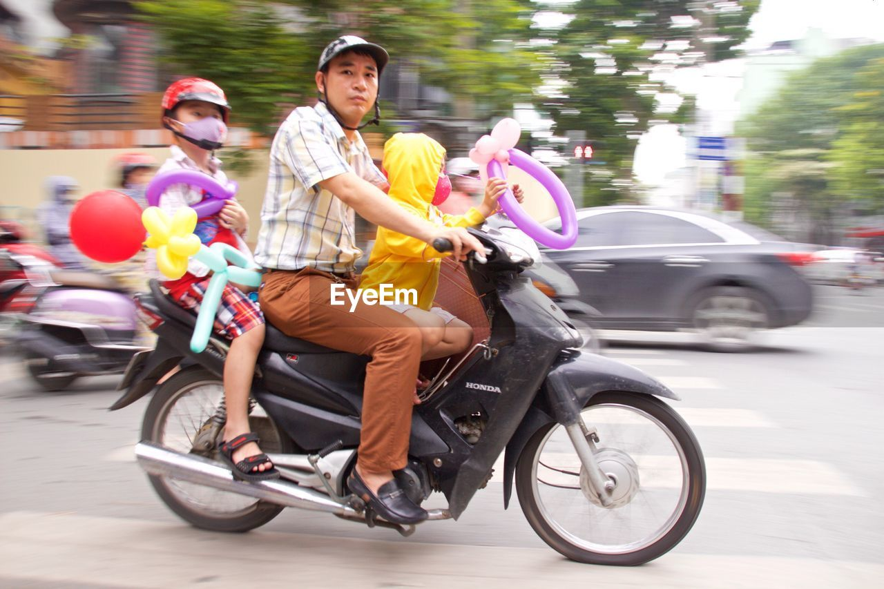 transportation, mode of transport, street, land vehicle, motorcycle, outdoors, helmet, real people, car, day, road, two people, headwear, young adult, young women, city