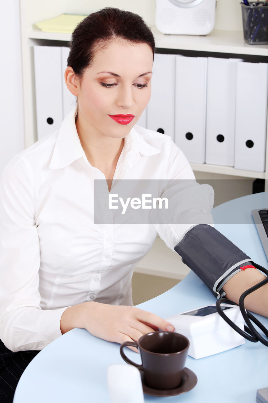 Young Woman Checking Blood Pressure Against White Background