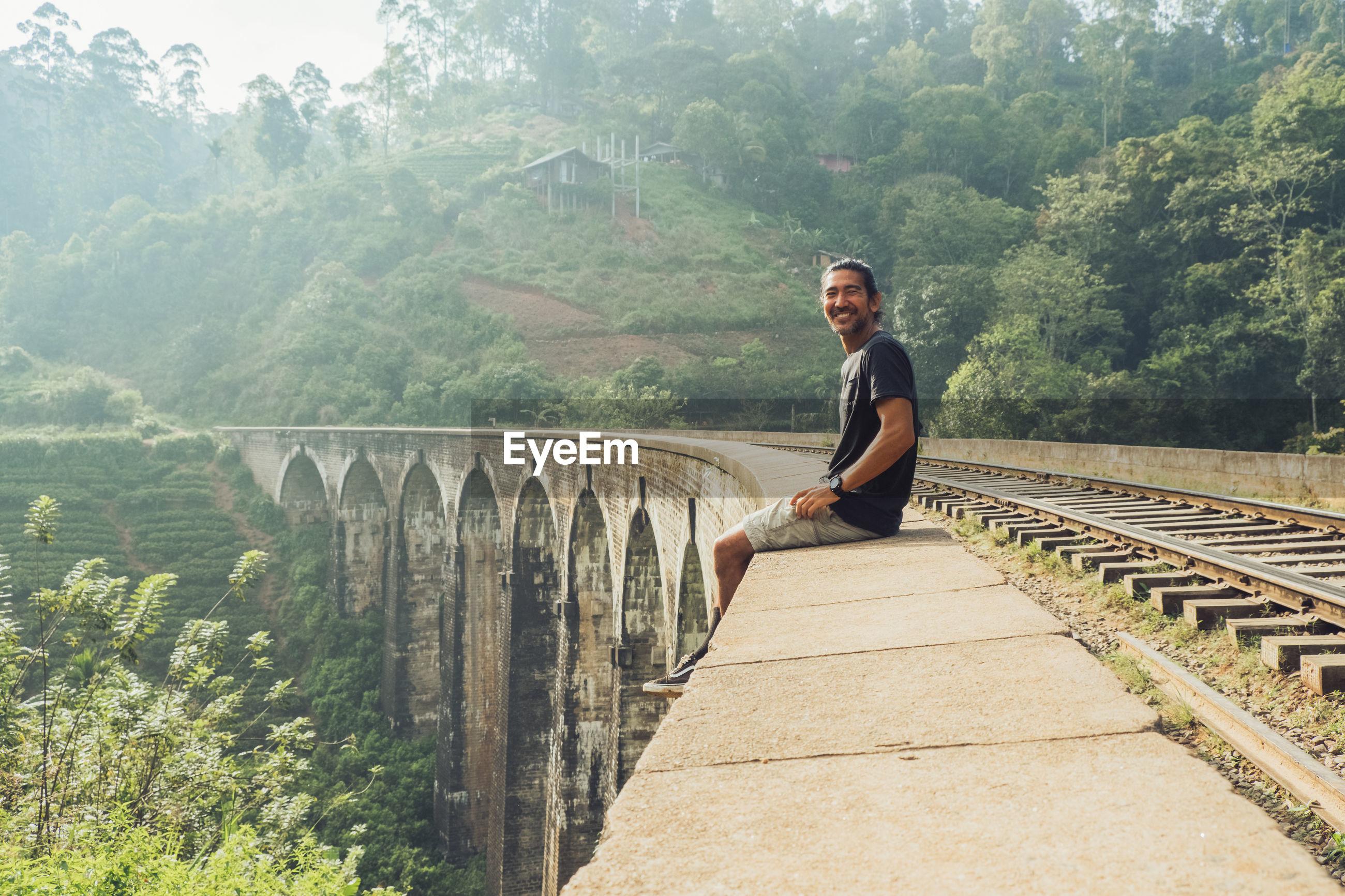 FULL LENGTH OF MAN ON BRIDGE AGAINST MOUNTAIN