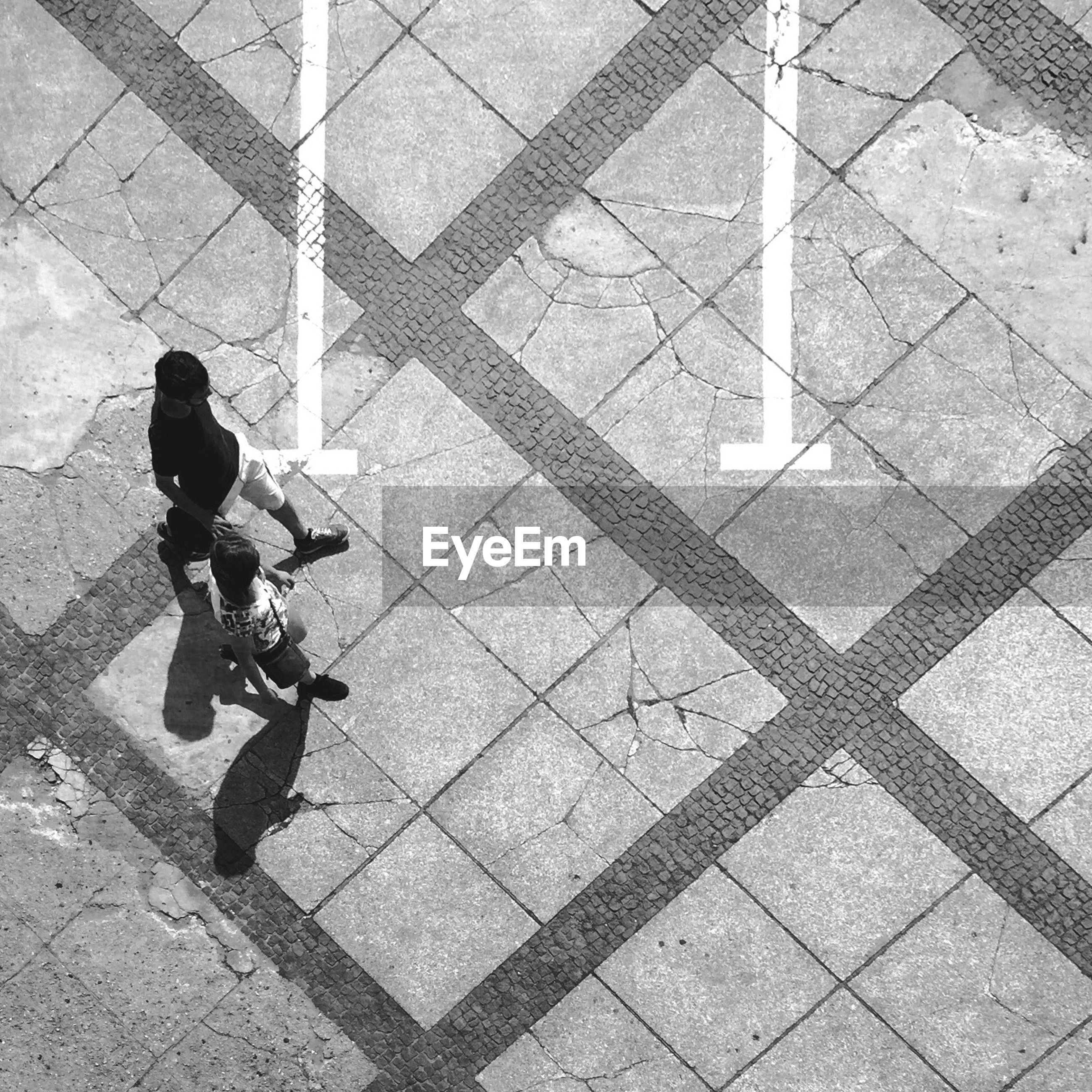 High angle view of people walking on cobblestone street