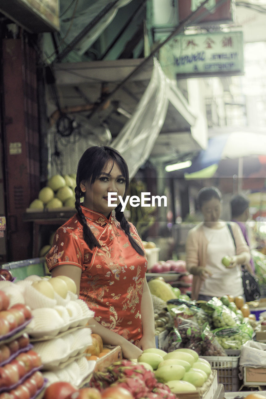 Portrait Of Young Woman While Standing By Market Stalls