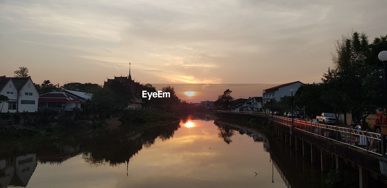 sky, water, architecture, built structure, sunset, building exterior, reflection, tree, cloud - sky, building, plant, nature, house, residential district, no people, waterfront, city, orange color, outdoors, canal
