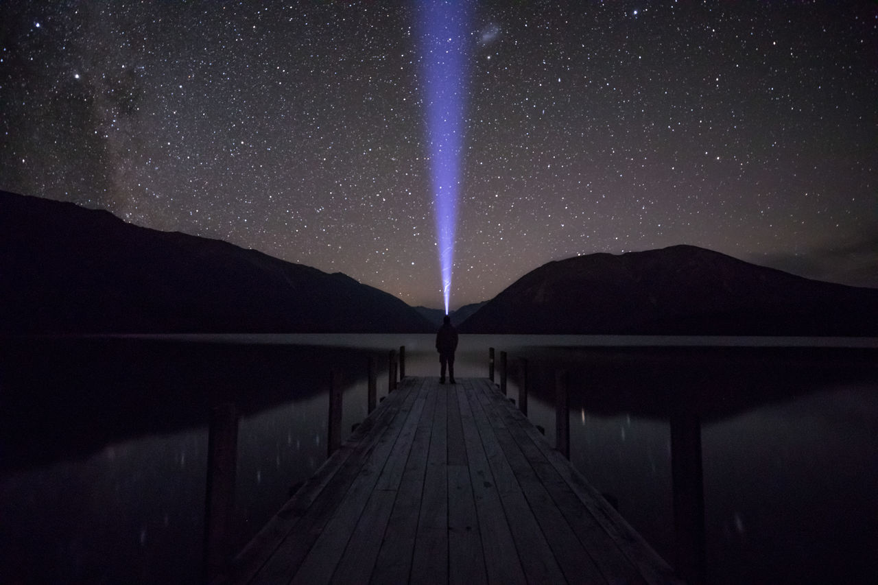 Man Standing Amidst Lake On Pier Against Star Field
