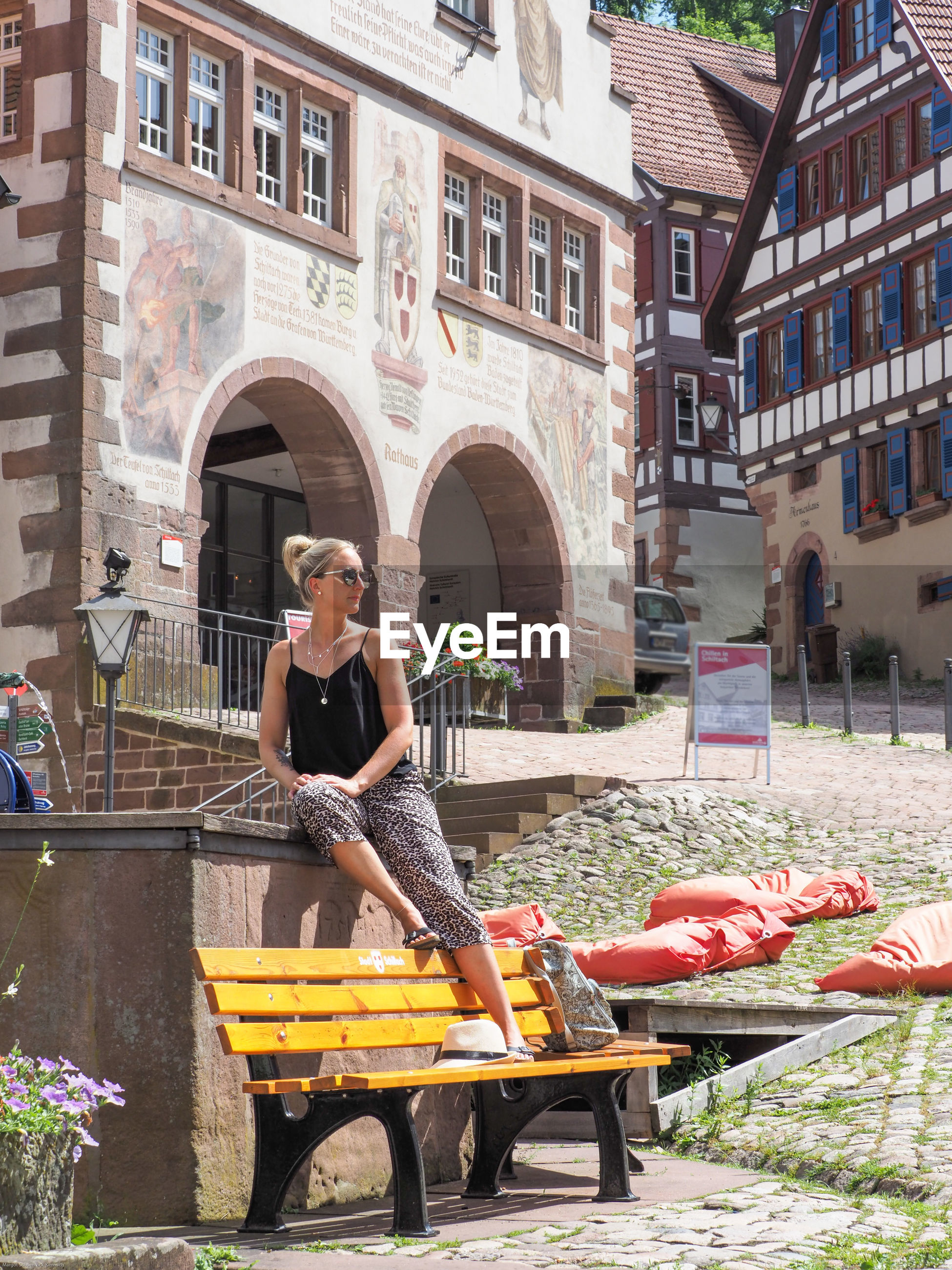 FULL LENGTH OF WOMAN SITTING ON SEAT AGAINST BUILDING