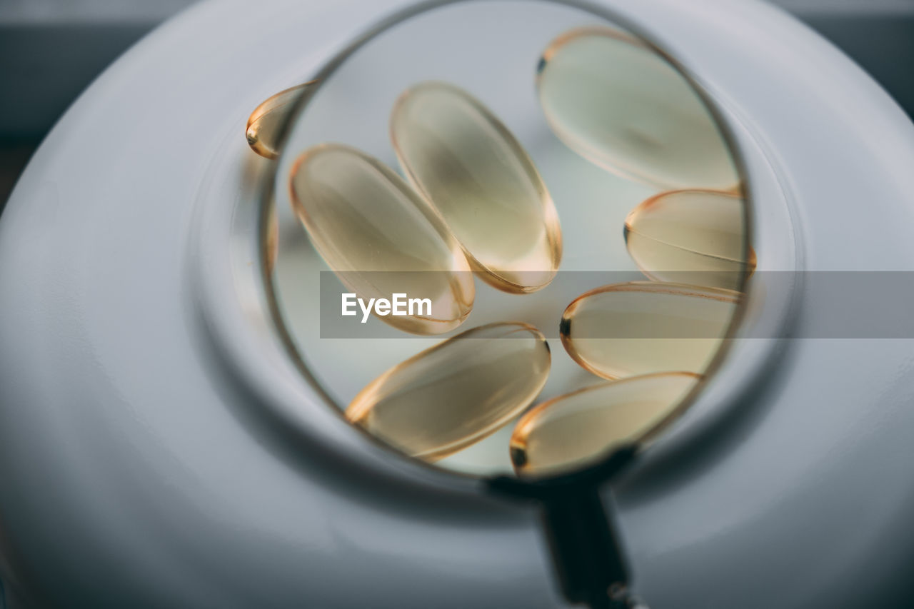 Yellow transparent omega 3 capsules under a magnifying glass. drug development concept