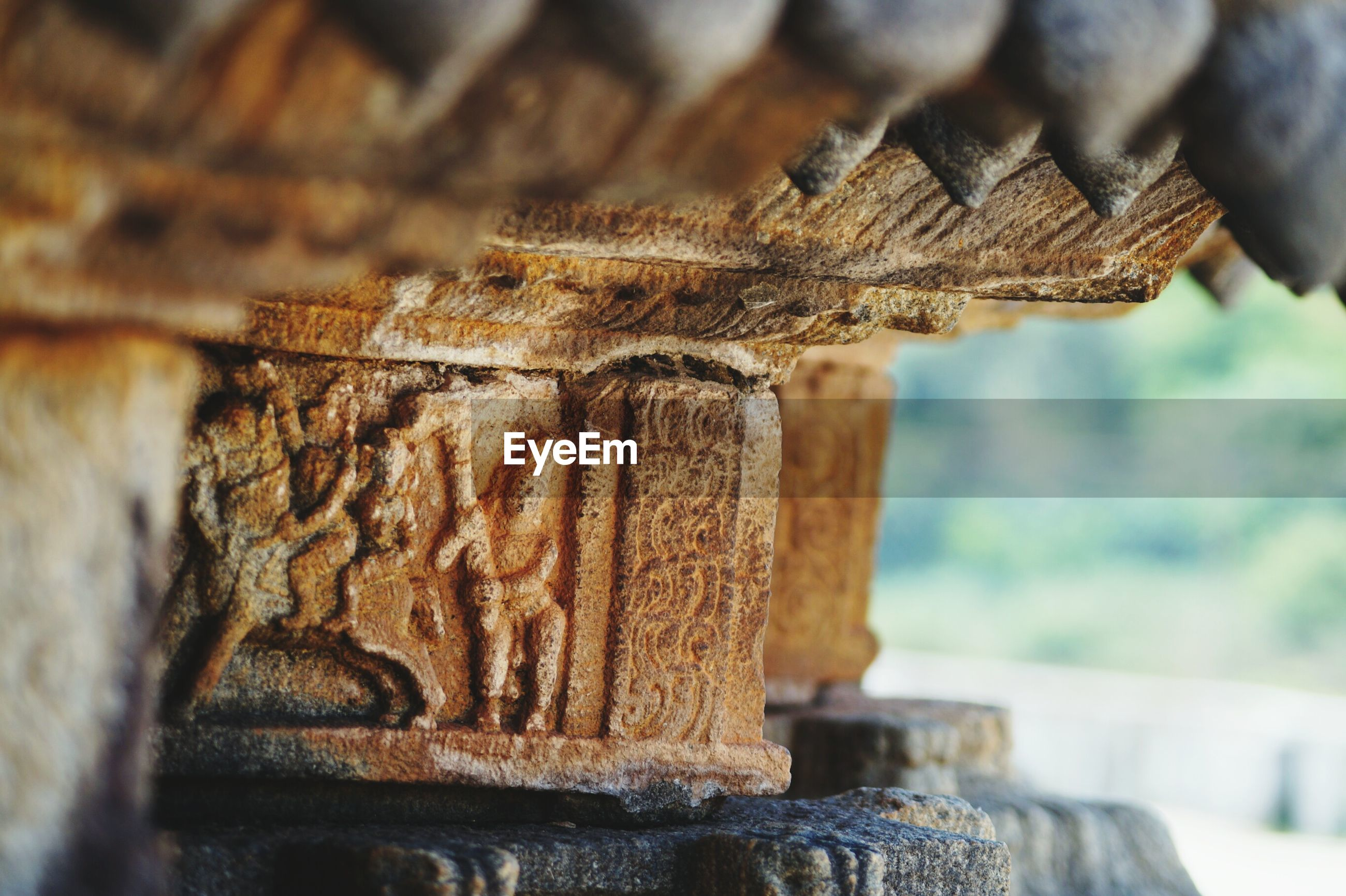 focus on foreground, close-up, selective focus, wood - material, old, day, animal themes, art and craft, weathered, outdoors, wall - building feature, art, built structure, no people, animals in the wild, stone material, rusty, architecture, one animal, religion