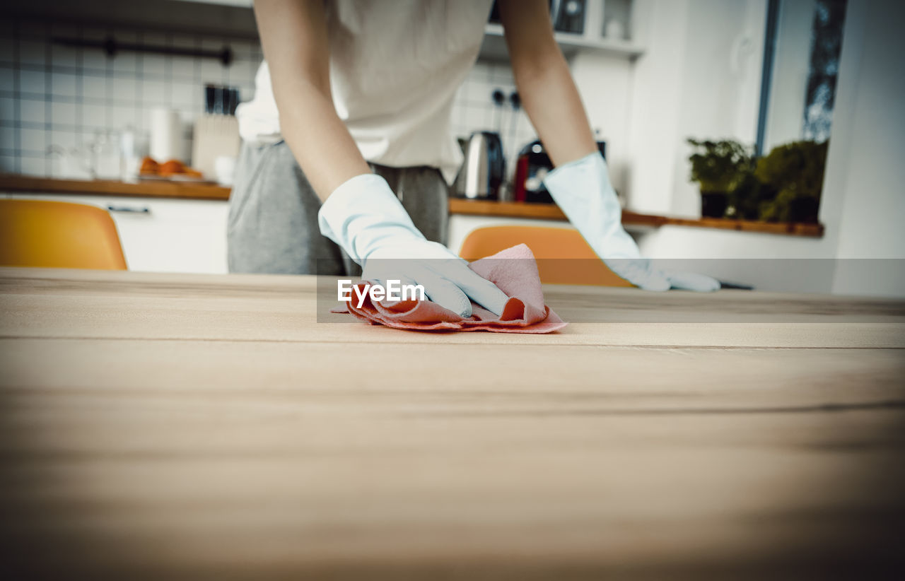 Midsection of woman cleaning wooden table at home