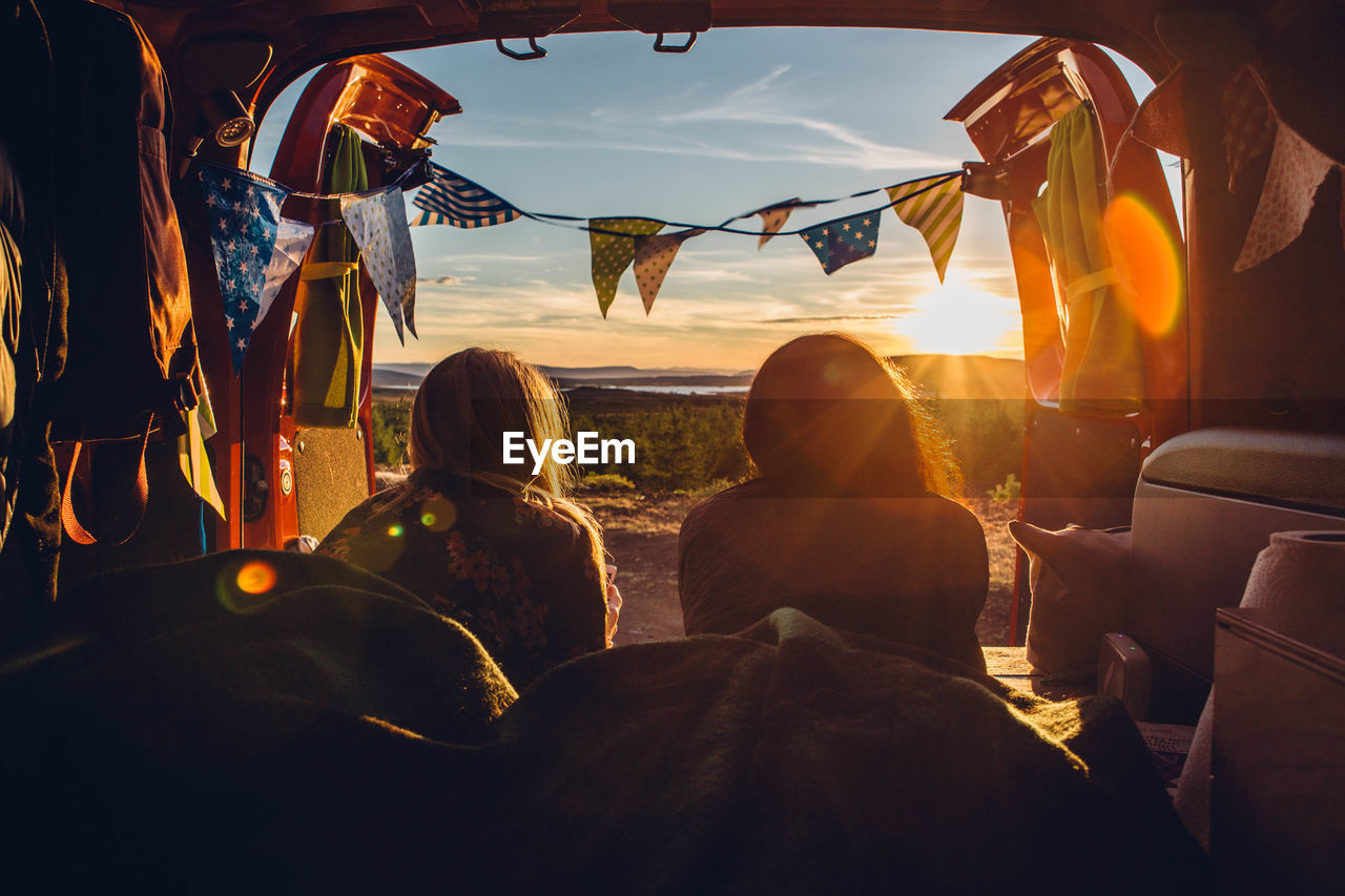 real people, sitting, nature, vehicle interior, lifestyles, group of people, leisure activity, women, rear view, adult, sky, men, people, travel, sunlight, sunset, transportation, car, mode of transportation, group, lens flare, outdoors