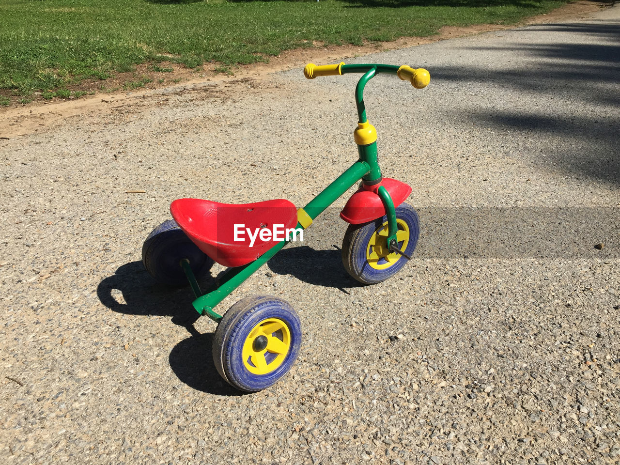 transportation, childhood, tricycle, sunlight, toy, day, road, nature, high angle view, land vehicle, shadow, absence, bicycle, mode of transportation, outdoors, scooter, city, land, multi colored, wheel