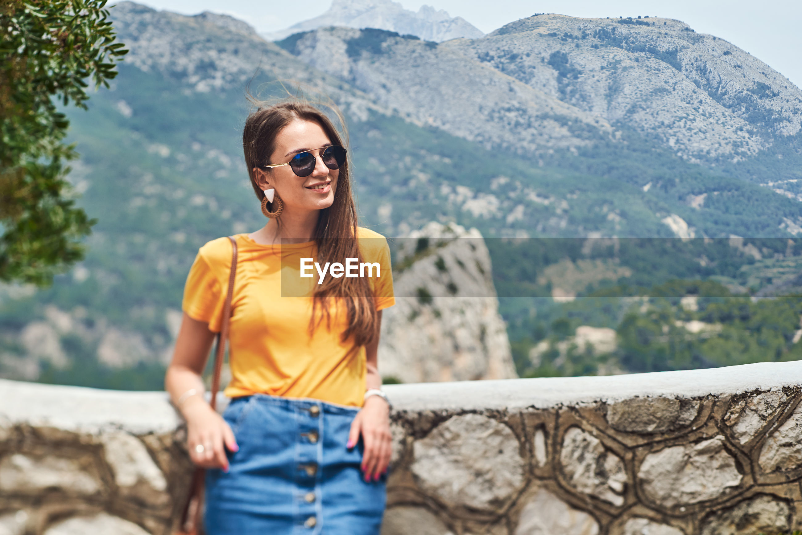 WOMAN WEARING SUNGLASSES STANDING ON MOUNTAIN