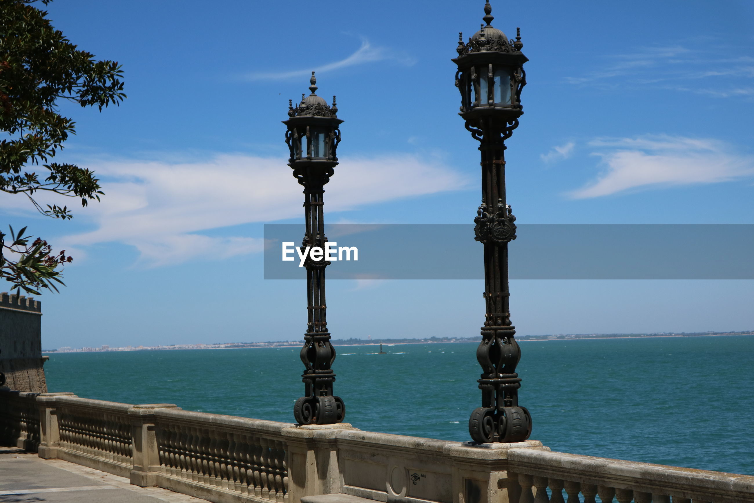 View of street light by sea against sky