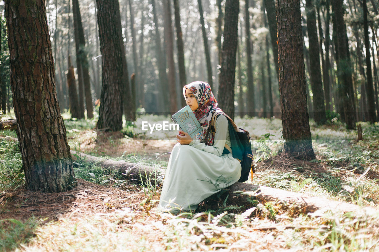 forest, tree, adults only, woodland, tree trunk, nature, one person, adult, only women, one woman only, people, women, outdoors, day, young adult, adventure, full length, one young woman only, smiling, young women