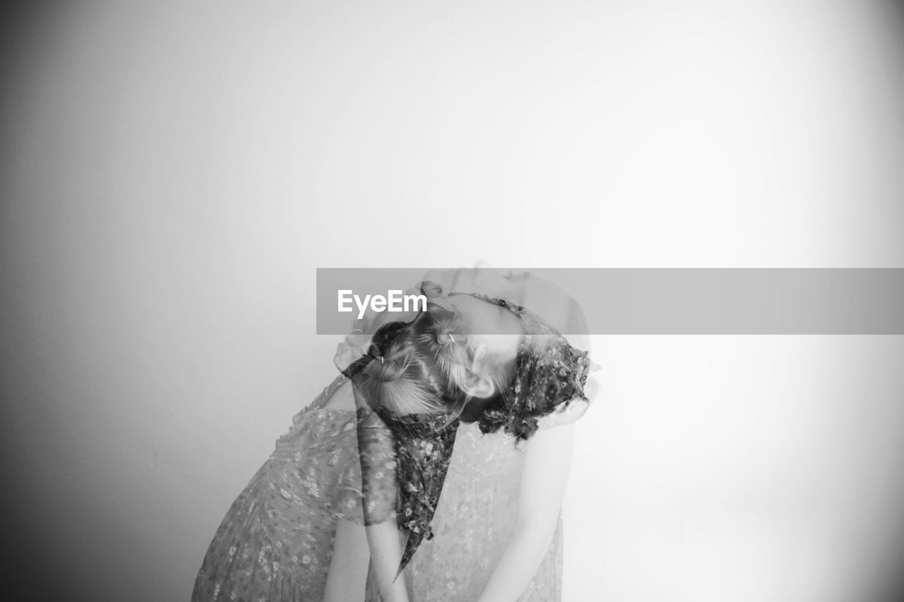 Double exposure of woman and dog against white background