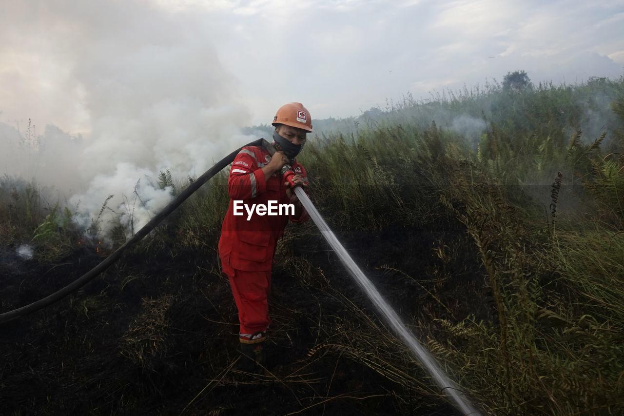 Rear view of firefighter working on field