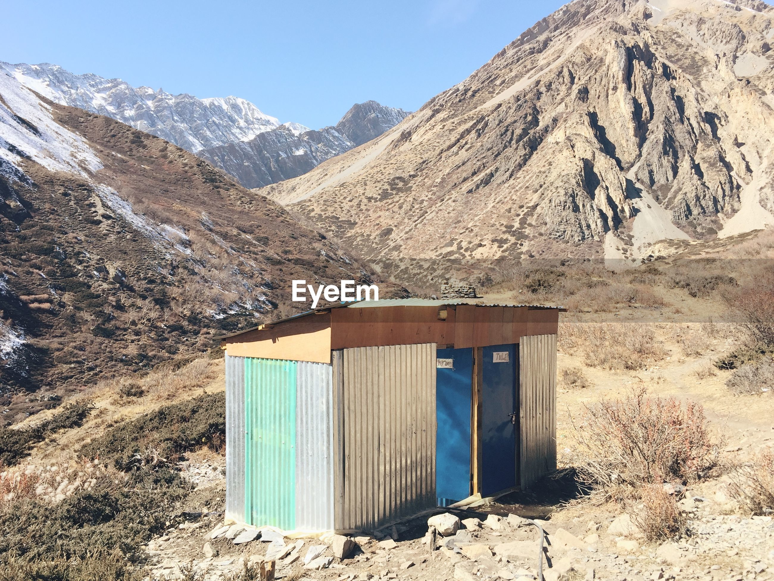 Outhouse on field against mountains