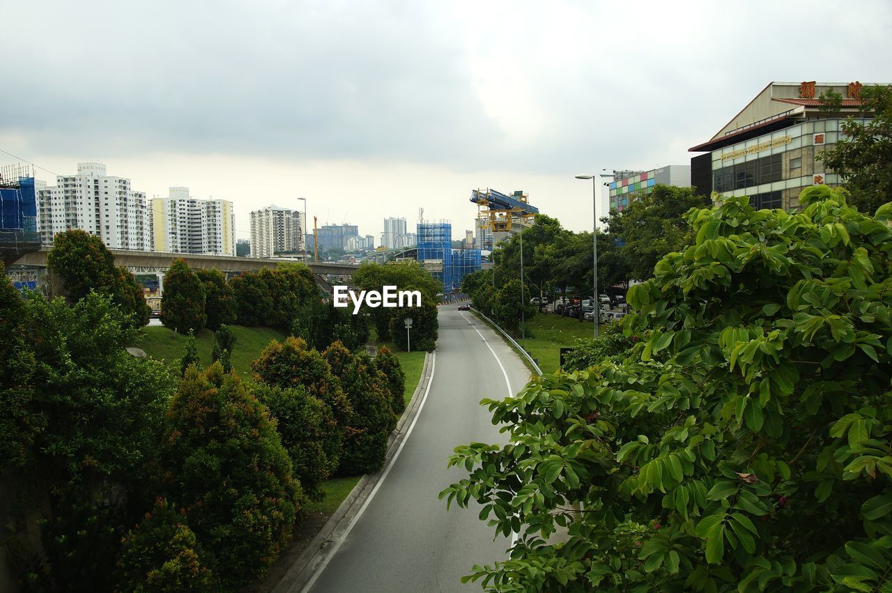 HIGH ANGLE VIEW OF ROAD BY BUILDINGS AGAINST SKY