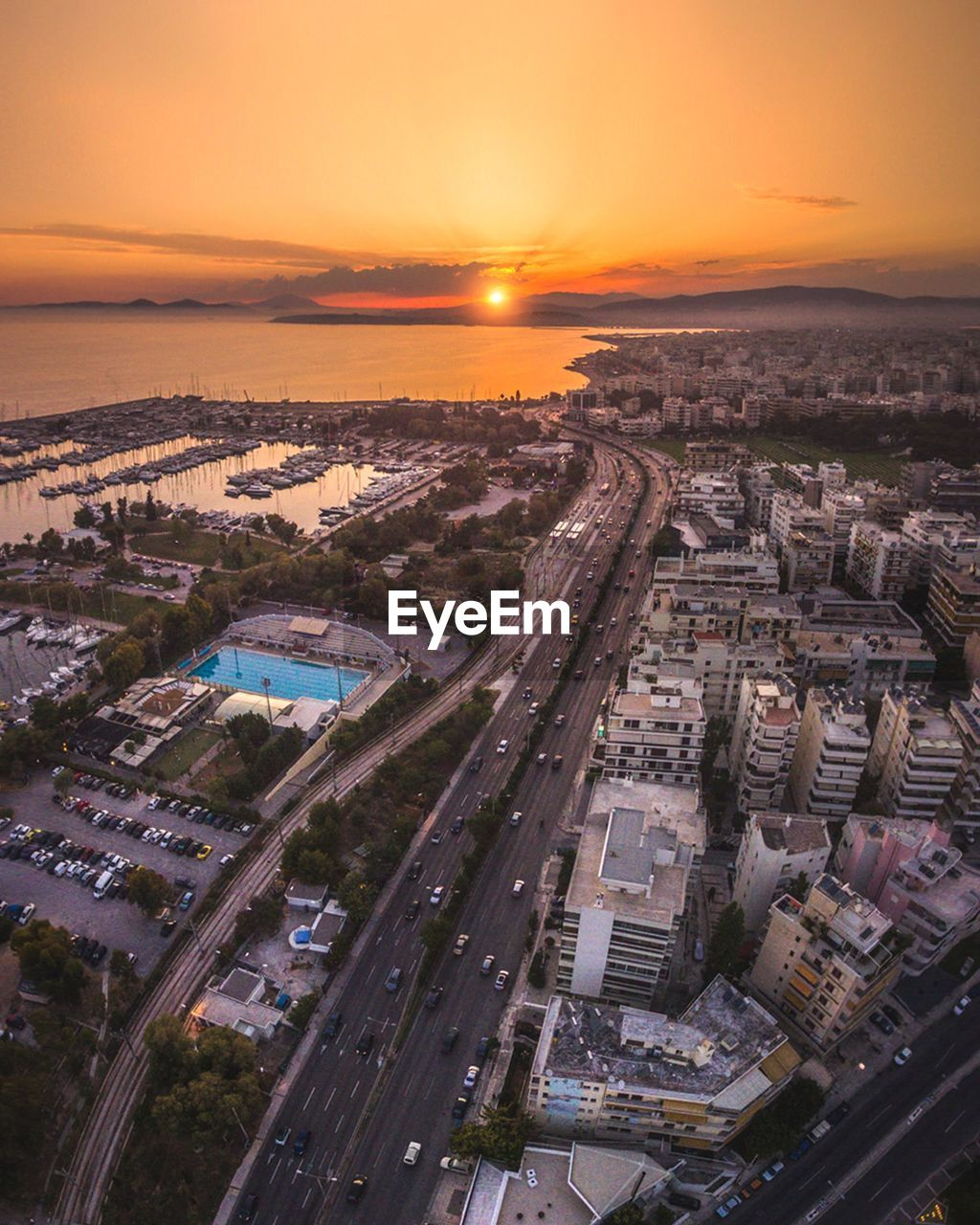 Aerial View Of City By Sea Against Sky During Sunset